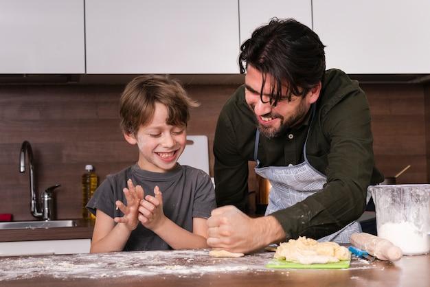 Низкий угол маленький мальчик с отцом раскатывает тесто