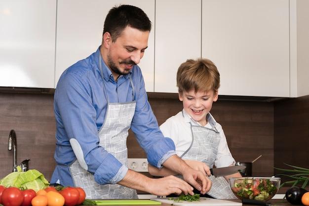 低角度のお父さんと息子の野菜を切る