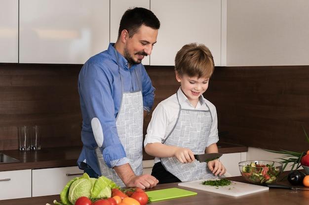 高角度のお父さんと息子の野菜を切る
