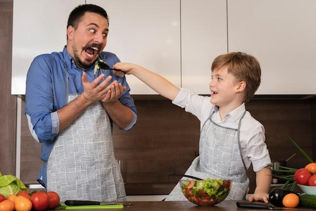 Сын дает папе попробовать салат