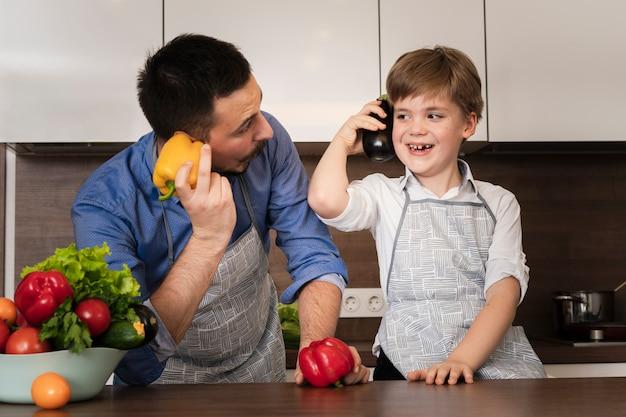 父と息子が野菜で遊んで