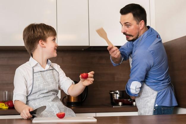 Отец и сын играют на кухне во время приготовления