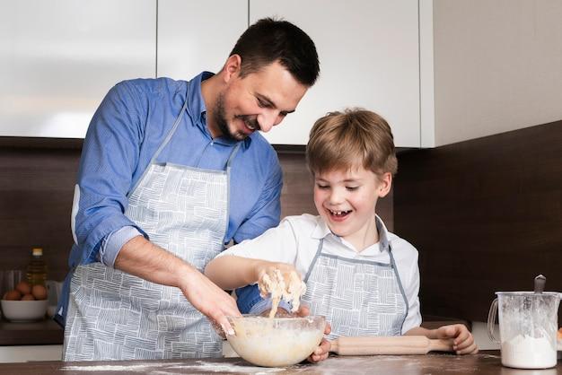 Низкий угол смайлик отец и сын, делая тесто