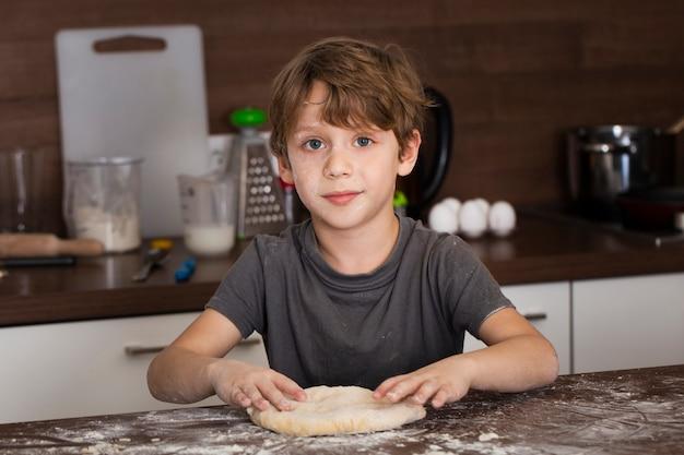 Высокий угол маленький мальчик делает тесто