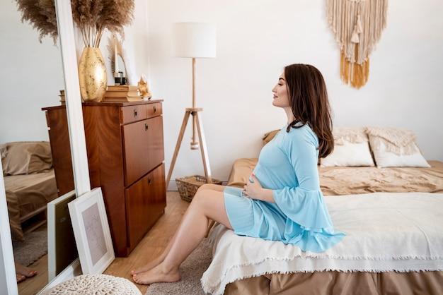 Беременная женщина сидит в вид сбоку и смотрит в зеркало
