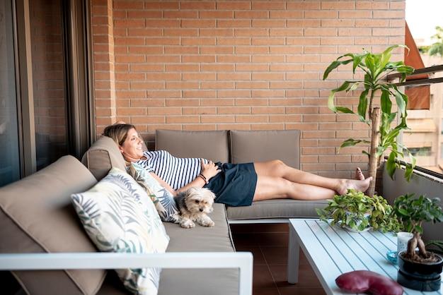 妊娠中の女性を敷設し、ソファでリラックス