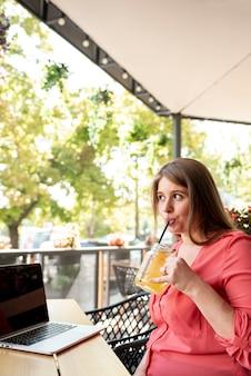 Средний выстрел женщина с ноутбуком, пить сок