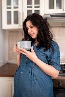 Средний выстрел беременной женщины с миской на кухне