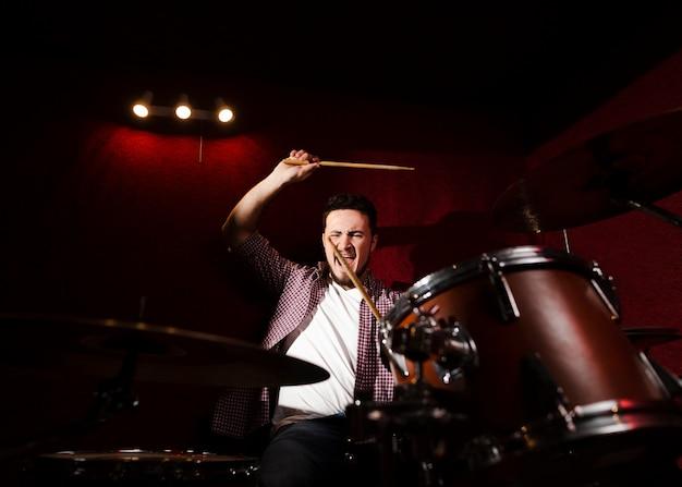 ドラムを演奏し、ドラムスティックでなでる男