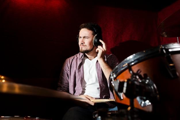 フロントビューの男がドラムを演奏し、面白い顔を作る