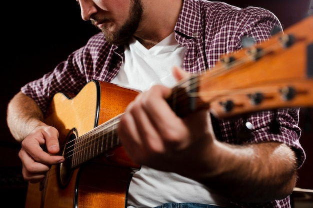 Затуманенное акустическая гитара и парень играет крупным планом