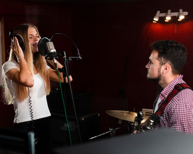 Женщина поет в микрофон и парень играет на гитаре