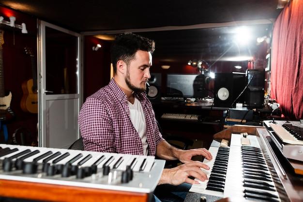 Боком человек играет на клавиатуре в студии