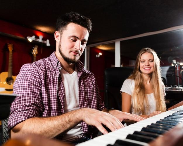 Мужчина играет на клавиатуре и улыбается женщина