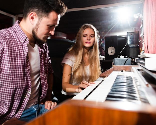 Женщина играет на клавиатуре и мужчина смотрит на инструмент