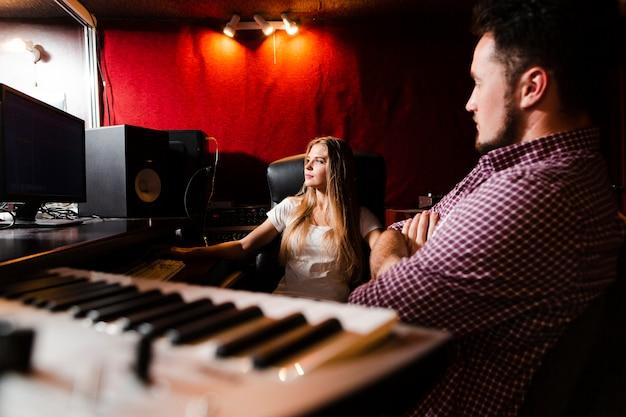 Клавиатура крупным планом и люди, осваивающие песни