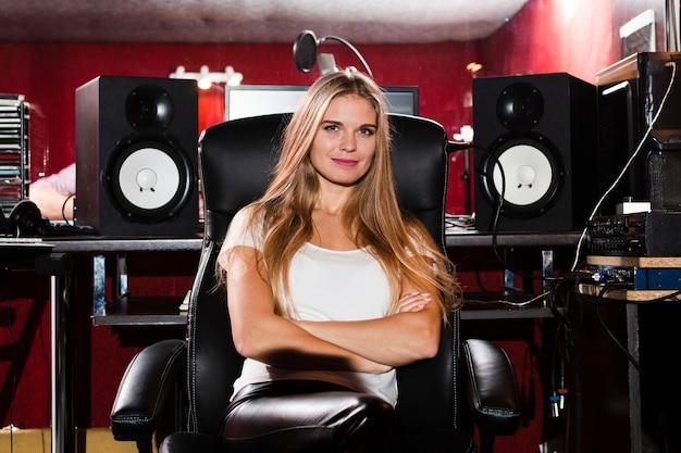 Вид спереди женщина со скрещенными руками сидит в студии