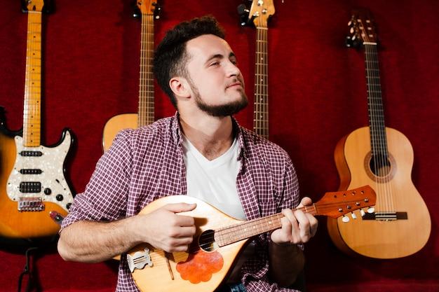 Парень играет на гитаре мандолины в студии