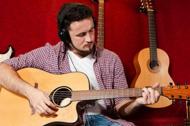 Парень играет на акустической гитаре в студии