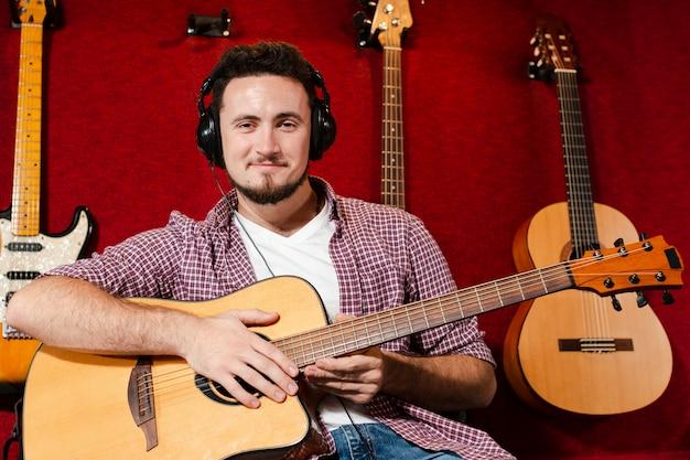 Парень сидит и держит гитару в студии