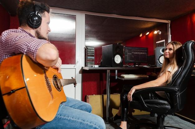Крупный мужчина играет на гитаре в студии