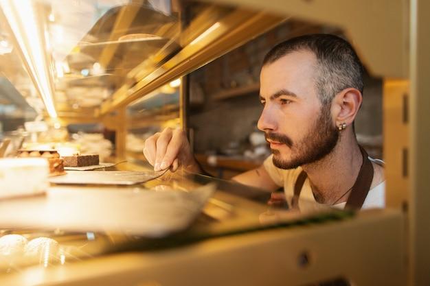 男性労働者がコーヒーショップの製品をチェック
