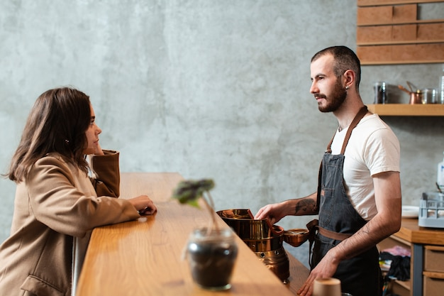 Мужчина готовит кофе и разговаривает с женщиной