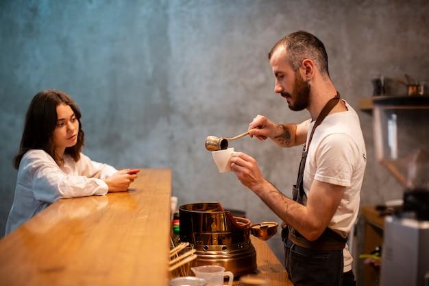 待っている顧客のカップにコーヒーを注ぐ男