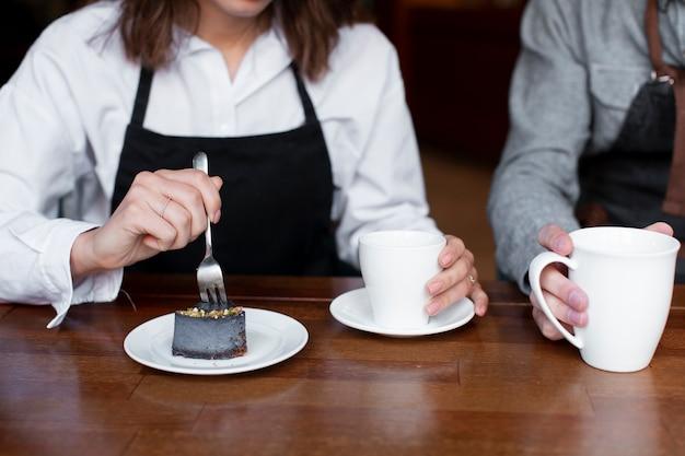 コーヒーのカップを保持しているカップルのクローズアップ