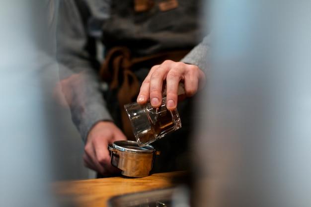 ポットにコーヒーを注ぐ手のクローズアップ