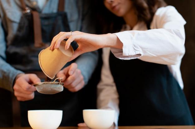 カップにコーヒーをふるう女性のクローズアップ