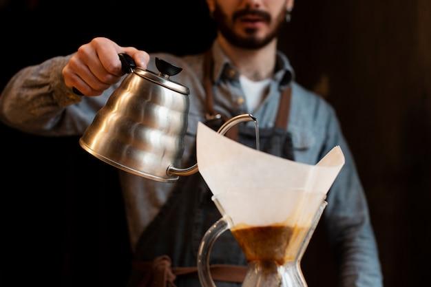 Крупный мужчина наливает кофе из горшка в фильтре