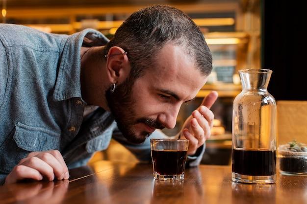 一杯のコーヒーの臭いがする男のクローズアップ