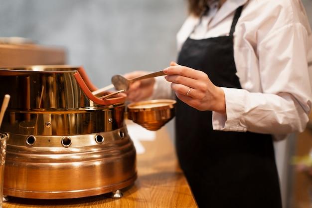 コーヒーマシンで働く女性のクローズアップ