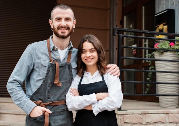 Пара в фартуках позирует возле кафе