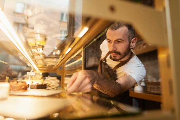 Мужчина в фартуке расставляет печеньки на дисплее