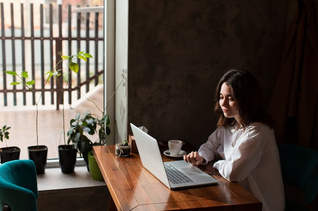 Женщина в кафе работает на ноутбуке