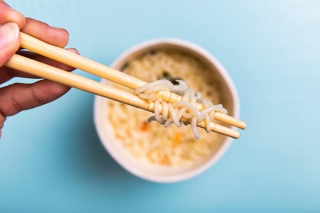 Крупным планом палочки для еды с лапшой