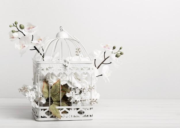 Белая клетка для птиц, полная цветов