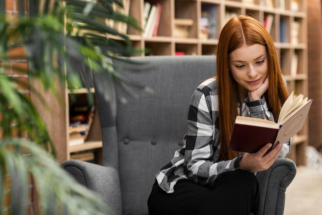 Симпатичная женщина читает книгу в помещении