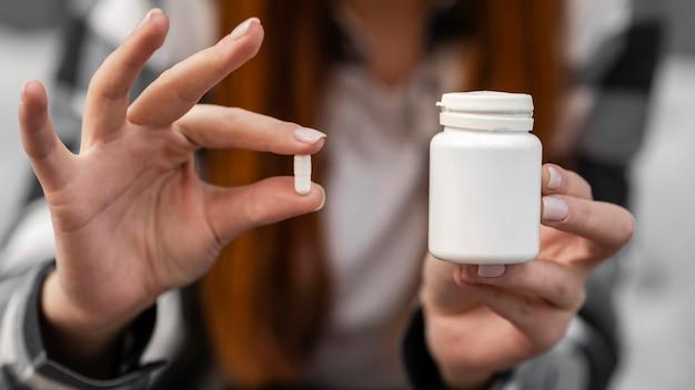 白い錠剤を保持している女性をクローズアップ