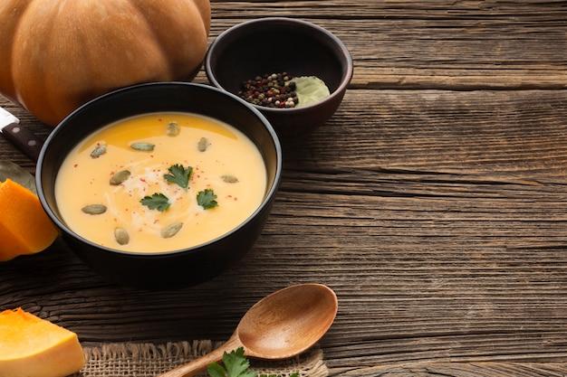 ボウルにカボチャとコピースペースと木のスプーンで高角度のカボチャのスープ