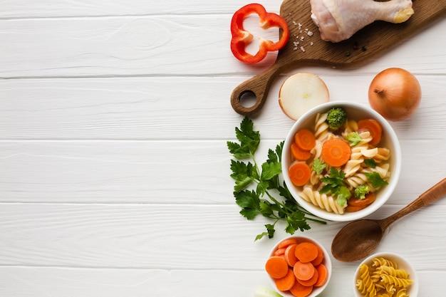 フラットレイアウトブロッコリーニンジンとフジッリコピースペースとまな板の上の鶏のモモ肉のボウル