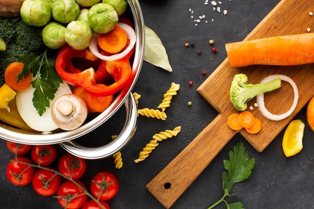 まな板の上のニンジンと鍋に野菜とチキンドラムスティックのフラットレイアウトミックス