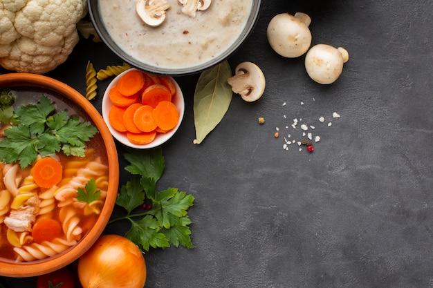 フジッリとコピースペースを持つフラットレイアウトマスルームビスクと野菜のスープ