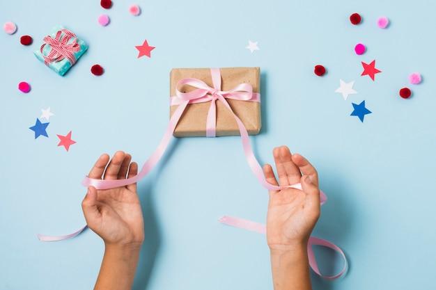 Вид сверху на руки, связывающие подарок с лентой