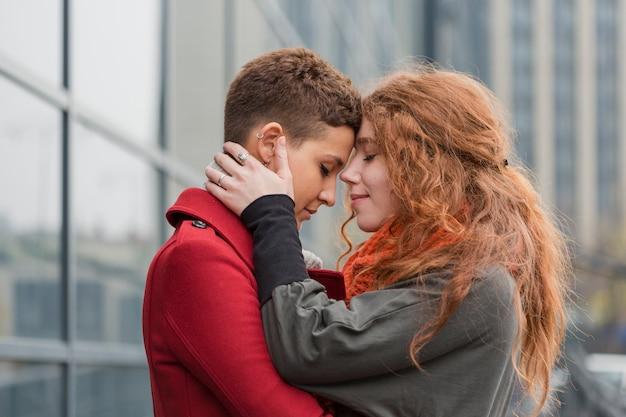 Очаровательные молодые женщины обнимают друг друга
