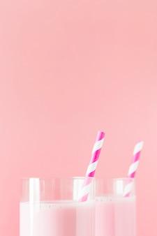 ストローでピンクのミルクセーキのクローズアップ
