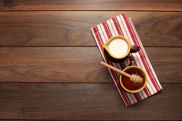 Вид сверху чашки с медом и молоком на столе