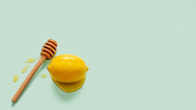有機レモンの横にある蜂蜜スティック
